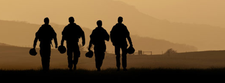 Military solidiers walking along mountain line